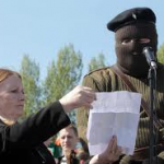 Marian Price helping to hold a statement for masked Real IRA man in April 2011