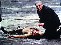 Fr Alec Reid administers the last rites to one of the murdered corporals