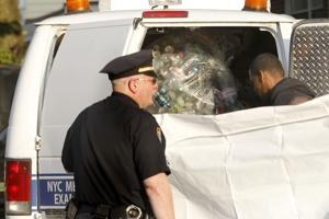 Police put the remains of Kevin Bell into the back of a truck with a bag of recycled bottles