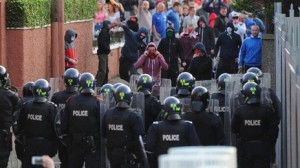 Police confront loyalist rioters in the Woodvale area of north Belfast on Saturday evening