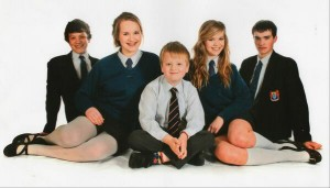 Aaron Macaulay sitting happily with his four older brothers and sisters for a sibling picture