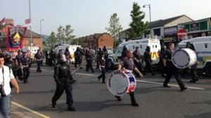 Orangemen pass Ardoyne shops in north Belfast amid a heavy police presence