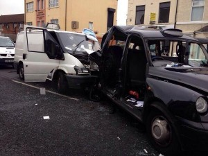 The scene of the accident in west Belfast where a white van has rear ended a black taxi