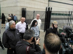 Willie Frazer with Jamie Bryson behind him in flowing locks and with tape over his mouth