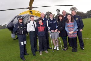 Caolan McCluskey and family with emergency services who helped save his leg