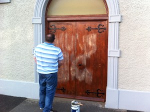 A member of the congregation paints out iRA graffiti on Presbyterian Church