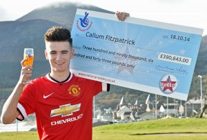 WHO'S A LUCKY BOY...Callum Fitzpatrick with his winning cheque for £390,000