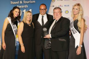 Peter McMinn, MD of Travel Solutions and Julie Magill, Operations Director of Travel Solutions receive their award for 'Best Short Break Tours Operator' from Peter Friedrich of TravelCube