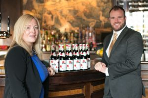 CHEERS… Manager of Berts Jazz Bar Lucy McConville and Gavin Carroll from The Merchant Hotel receive delivery of this year's new vintage Beaujolais Nouveau 2014.