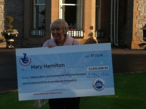 Bannons shopworker Mary Hamilton with her cheque for almost £13 million