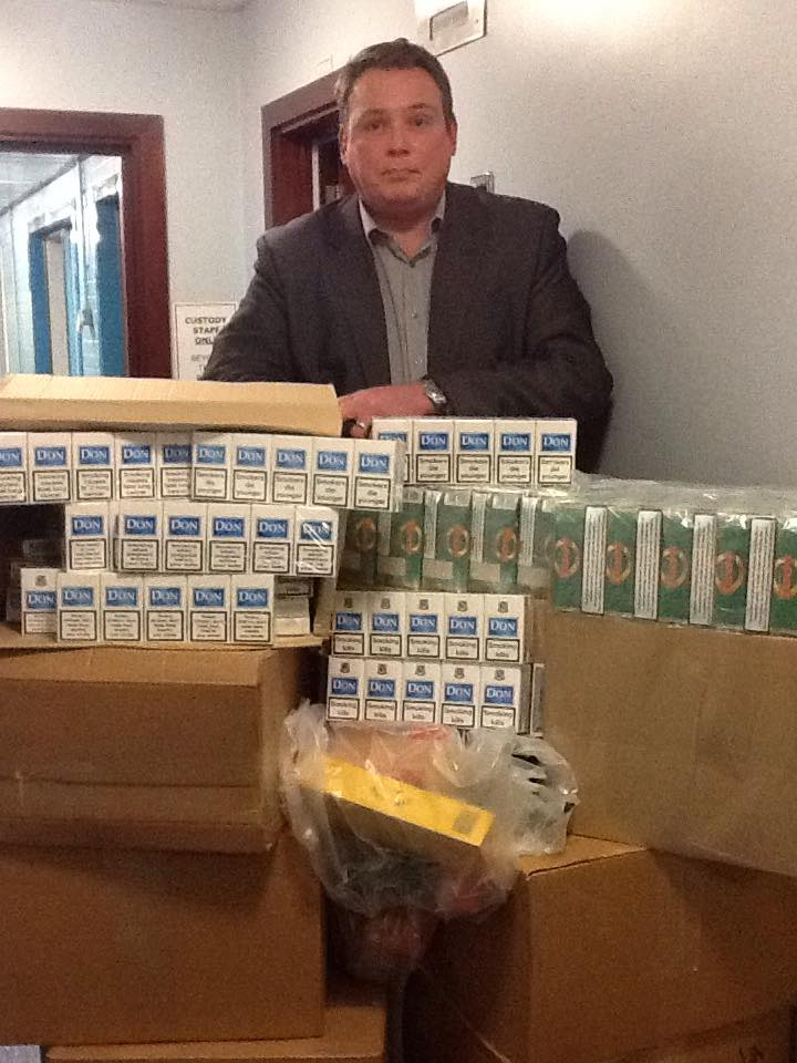 Detective Inspector Pete Mullan is pictured with some of the seized tobacco products.