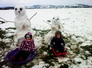 Children build a snowman on Saturday in Derriaghy