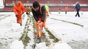 Ground staff clearing the snow at Windsor Park in south Belfast