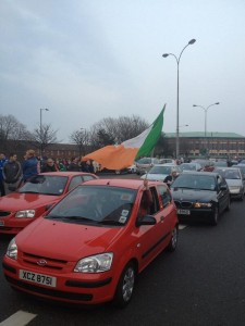 Crowds gather on Falls Road as a cavalcade of cars brings west Belfast to a standstill