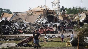 People walk near destroyed buildings and vehicles after a tornado struck Moore, Oklahoma, near Oklahoma City,