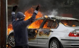 A silver BMW 3-Series car set alight during rioting in Ardoyne