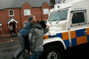 Sinn Fein MLA Gerry Kelly carried by PSNI landrover during Tour of the North parade last summer