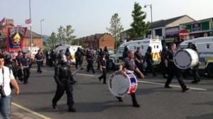 Orangemen pass Ardoyne shops in north Belfast amid a heavy police presence