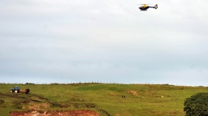 A PSNI helicopter circles over the scene of the farm tragedy accident in Castlewellan, Co Down