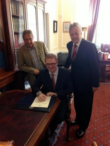 Simon Hamilton signs in as the new Stormont Finance Minister watched by First Minister Peter Robinson and outgoing minister Sammy Wilson