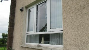 The smashed window of a Protestant family's home in Kells Avenue, west Belfast