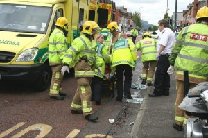 Paramedics and fire crews help to stretcher an injured person to an ambulance in east Belfast