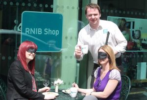 RNIB Northern Ireland's Joe Kenny serves up the 'Dining in the Dark' challenge to Lucy Haugh and Ursula Comican from Fold Housing Association.