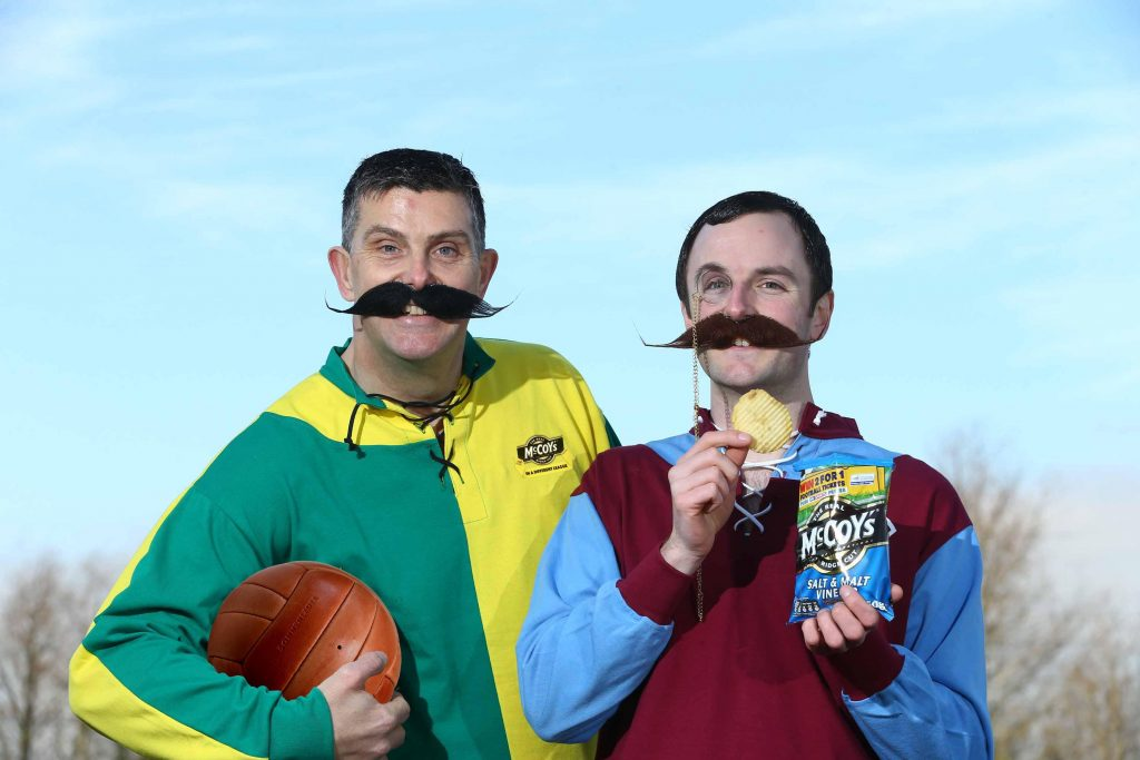 IN A DIFFERENT LEAGUE:  Rickie Watts (left) and John Baxter of KP Snacks (NI) donned some footie gear from yesteryear to launch McCoy's Crisps' tasty new deal with the oldest league in world football.