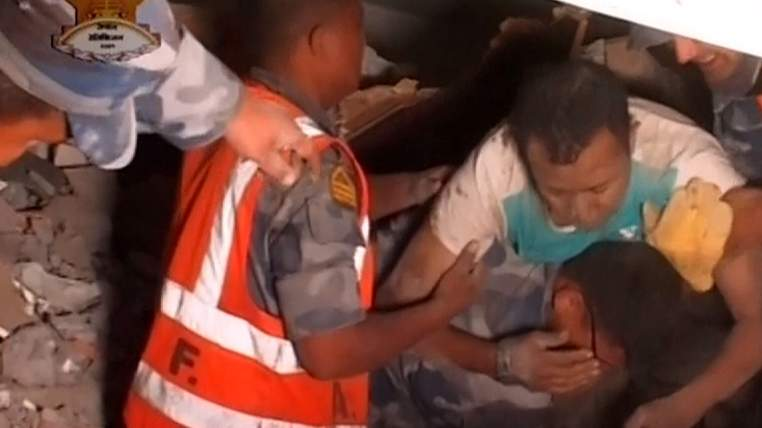 Rescue workers trying to pull people to safety after a massive earthquake in Nepal