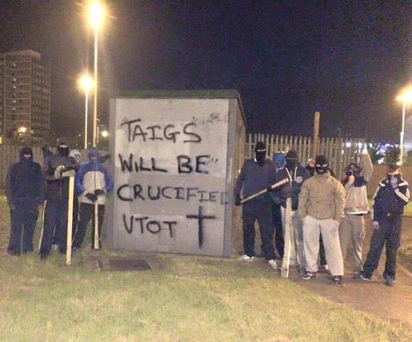 Masked loyalists beside a sinister message at Broadway roundabout in west Belfast