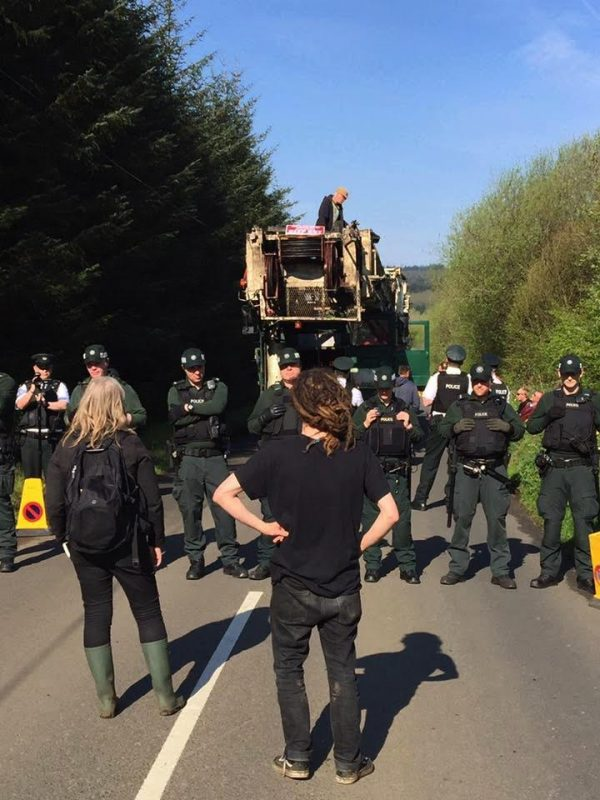 Tactical Support Group PSNI officers face down Stop The Drill campaigners on Paisley Road in Carrick