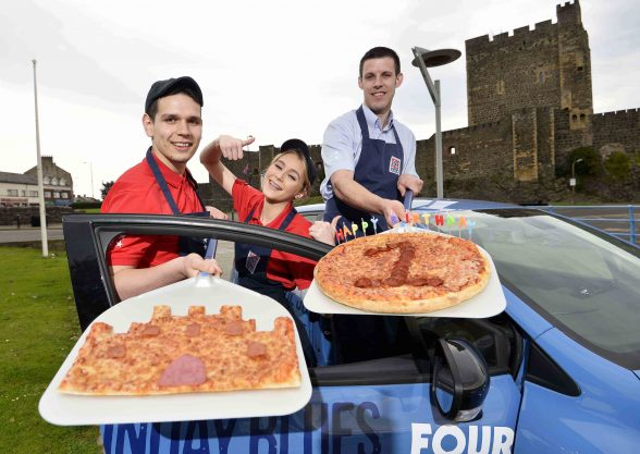 CASTLE DO NICELY!!! (l-r) Teofil-Stefan Sorban, Emma Gaw and Mark Givens (manager) of Four Star Pizza in Carrick celebrate the restaurant's first birthday with their very own Carrickfergus Castle pizza creation.  The store officially opened its doors on Marine Highway in September 2015 as part of a £150,000 investment which has created 20 jobs in the area