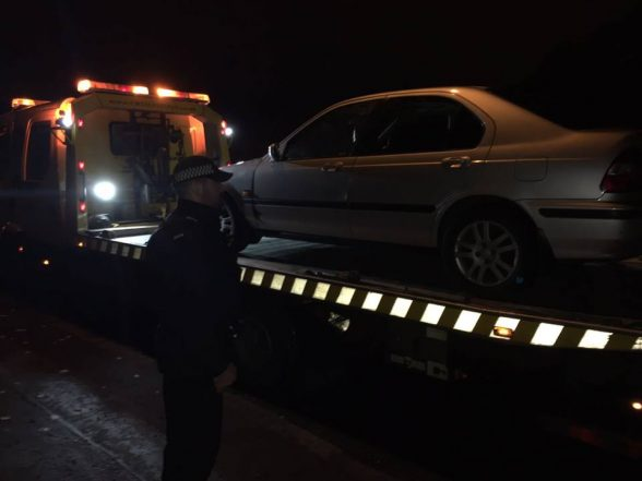 TSG officer watches on as a car which skidded into police checkpoint is seized and taken to car pound